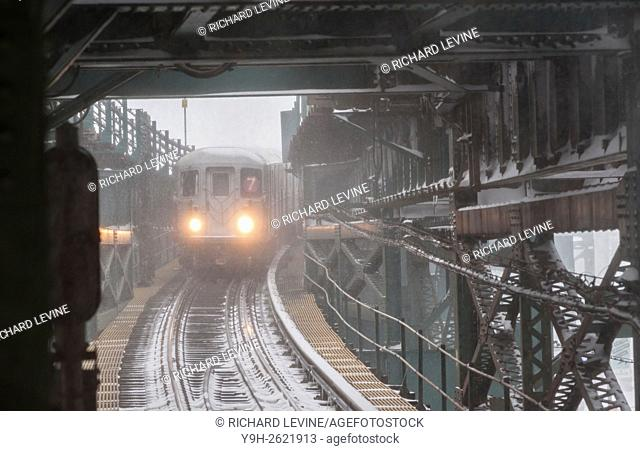 An elevated Flushing Line train arrives at the Queensboro Plaza station in New York during Winter Storm Jonas