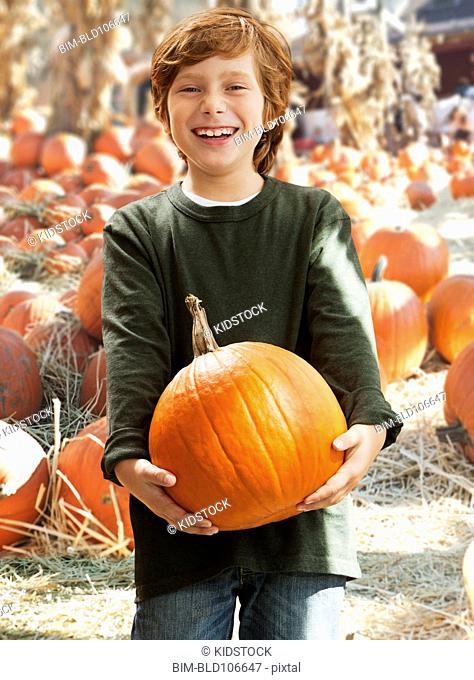 Caucasian boy holding pumpkin