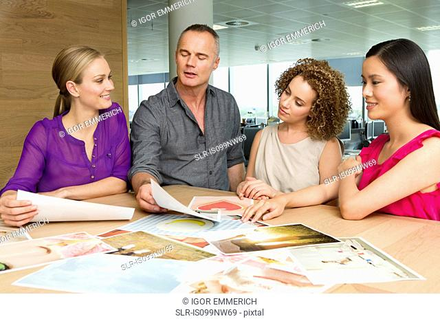 Fashion designers at desk looking at imagery