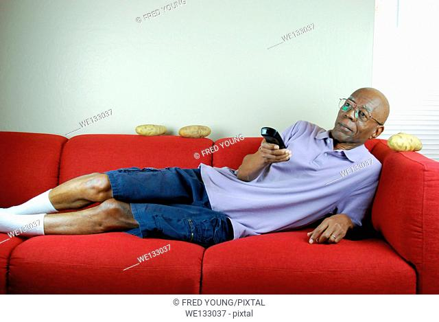 A senior citizen relaxing on a couch with a remote control in hand and potatoes on the couch