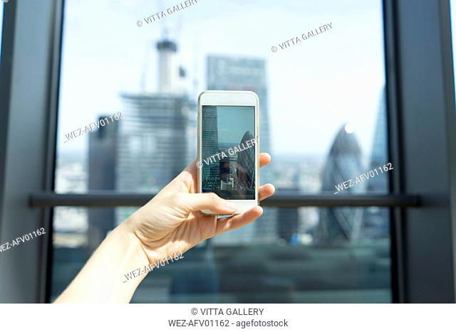 UK, London, woman's hand taking photo of skyscrapers of financial district with cell phone
