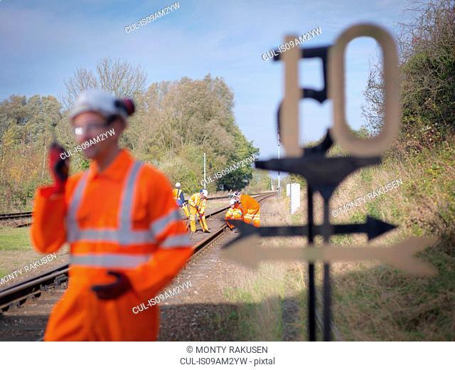 Railway worker using walkie talkie on railway track