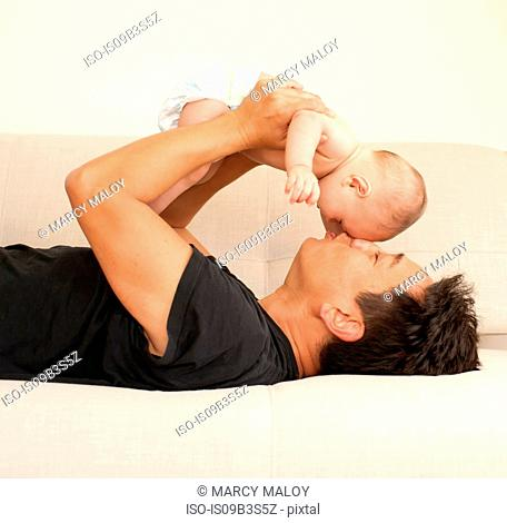 Mature man lying on bed holding baby son face to face