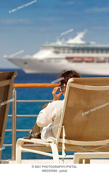 Woman with a cell phone on a deck, Cozumel, Mexico