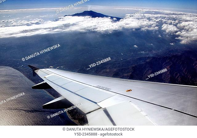 Passenger jet after departing from Catania airport, flying over Sicily, in background Etna volcano,Sicily and round horizon line, Sicily, Italy, Europe