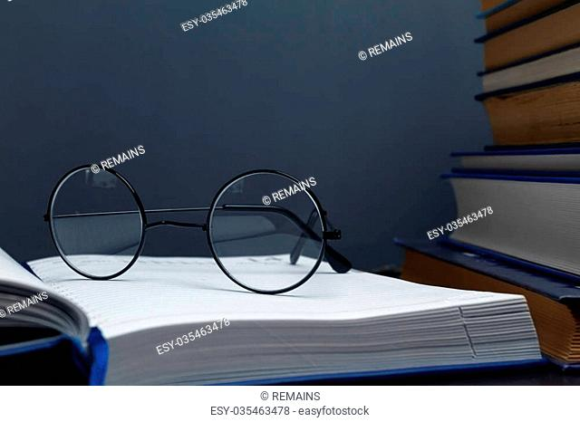 Stack of books and glasses on a blackboard background, space for text