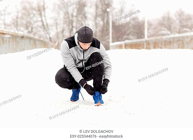 fitness, sport, people, music and healthy lifestyle concept - young man man in earphones tying shoe on winter bridge