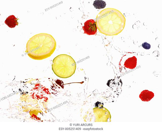 Studio shot of mixed fruit swirling through crystal clear water
