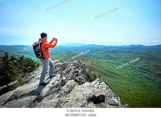 Male hiker taking smartphone photographs from ridge, Blue Ridge Mountains, North Carolina, USA