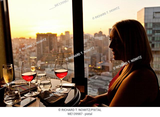 A young woman enjoys a glass of wine and a view of San Francisco from the lounge at the Marriott Marque Hotel, San Francisco, California