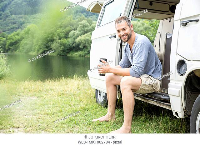 Smiling man sitting in a van at lakeside