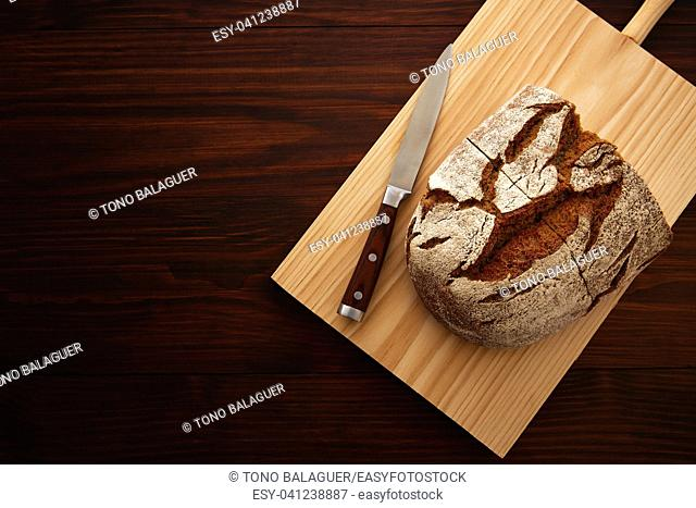 Rye bread and knife on board in dark wooden table top view