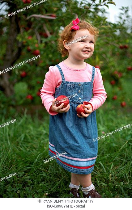 Girl standing in orchard holding apples