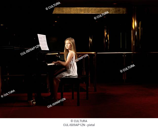 Portrait of girl playing piano on stage
