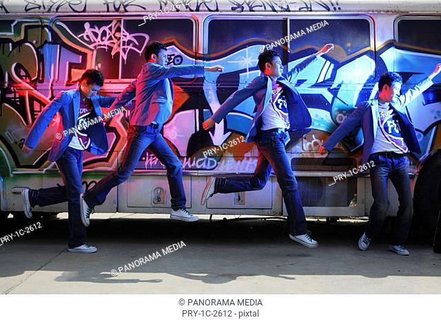 Young man jumping by painted bus