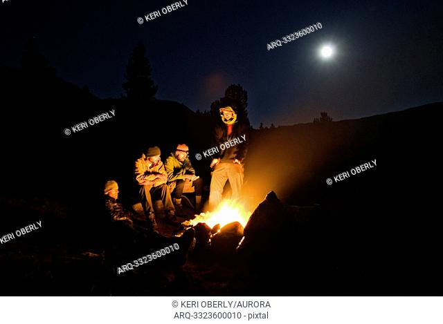 A group of campers sit around a camp fire for warmth in Yosemite, California