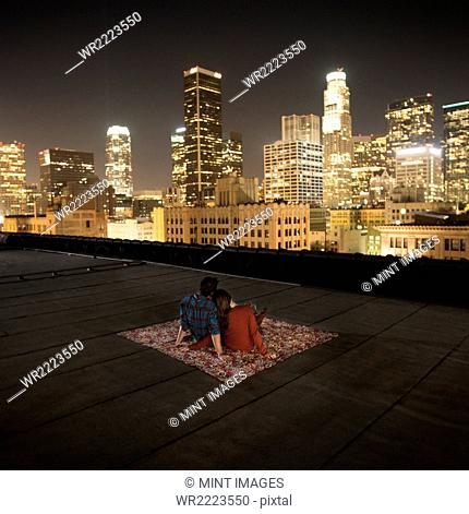 A couple sitting on a rug on a rooftop overlooking a city lit up at night