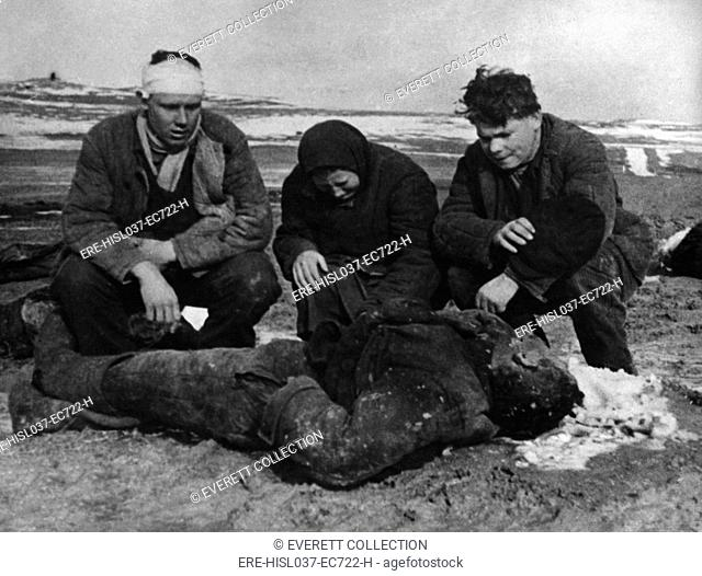 Aftermath of a German massacre of Soviets (Russians) in the Kerch Peninsula, Crimea. The Polyarush family kneel beside the body of their father