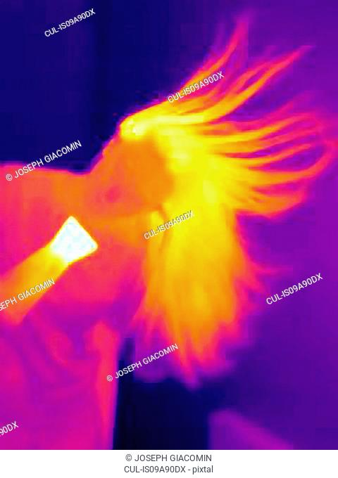 Thermal image of young woman drying her hair