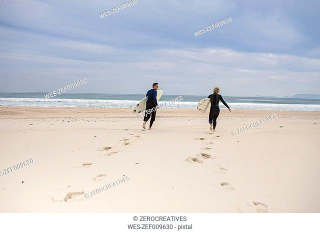 Couple with surfboards on the beach walking to the sea