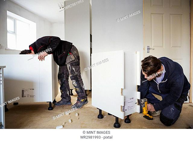 Two builders, building white kitchen units