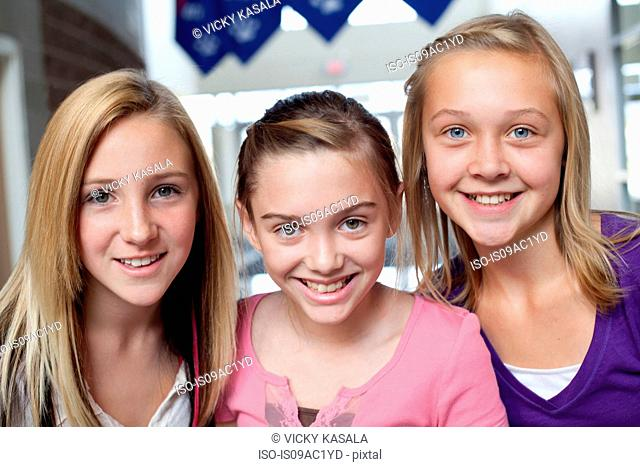 Close up portrait of three teen and pre-adolescent girls smiling