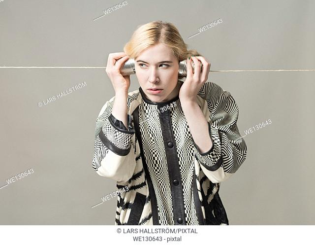 Blonde woman listening with tin can phone. Conceptual image of spying, surveillance and communication
