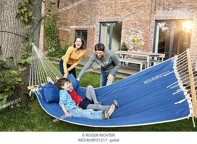 Happy family playing in hammock in garden of their home