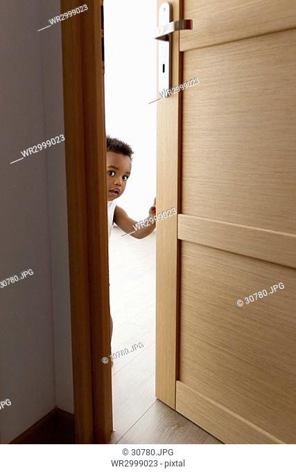 Young boy peeking through door