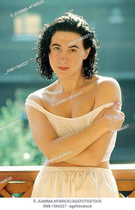 Beautiful young woman with his arms folded, looking at camera