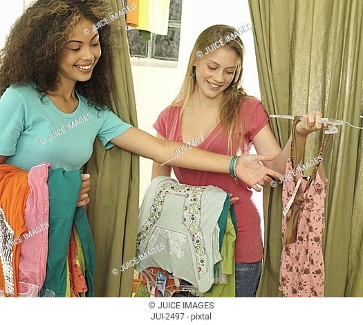 Two teenage girls 15-17 trying on new clothes in clothes shop fitting room, smiling