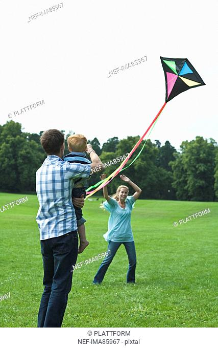 Parents and son playing with kite in park
