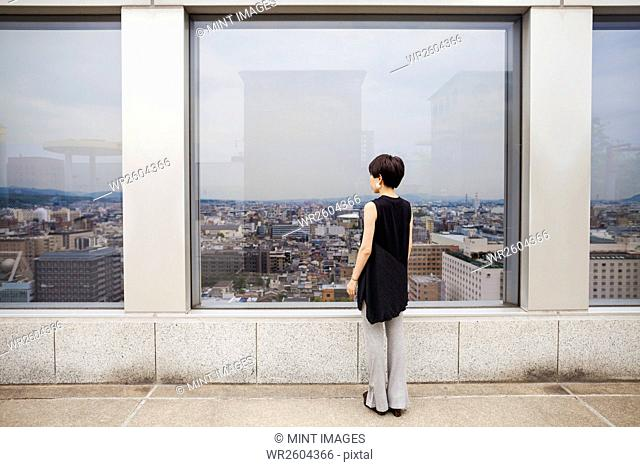 A woman standing looking over a city from a high viewing point
