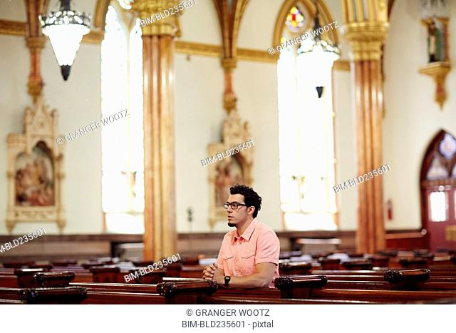 Kneeling Hispanic man praying in church pew