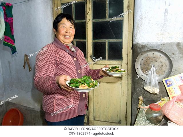 Farmer's wife holding cooked vegetable meal in farmhouse kitchen in village of Poli near Penglai, Shandong Province, China