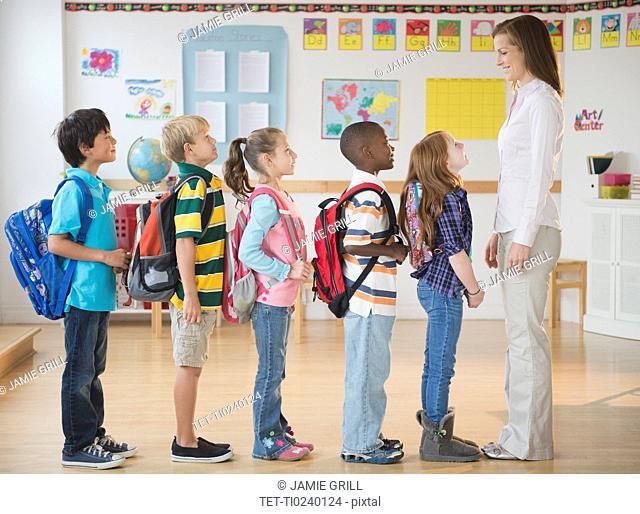 School children 8-9 with female teacher standing in row in classroom