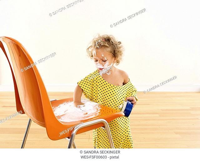 Little girl applying cream on chair