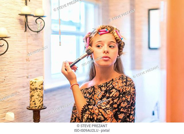 Teenager putting on make-up in bathroom