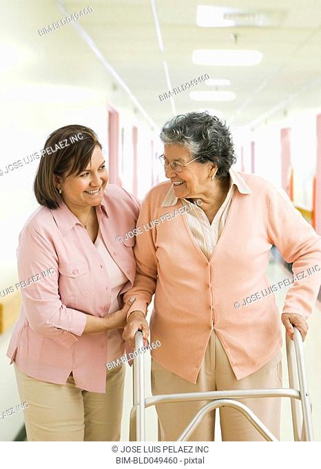 Hispanic woman helping mother walk