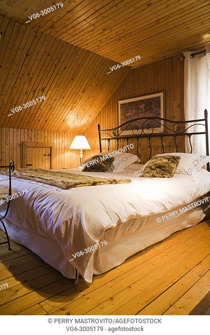 Bed with wrought iron headboard in the guest bedroom on the upstairs floor inside a 1920s cottage style old home. Quebec, Canada
