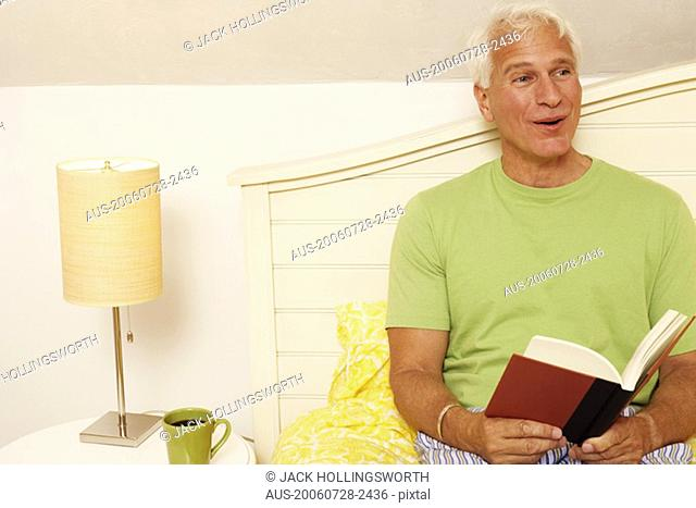 Close-up of a mature man sitting on the bed and holding a book