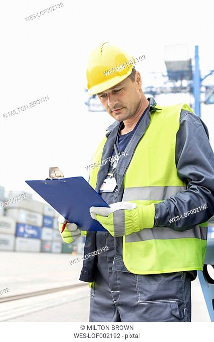 Man with clipboard wearing safety vest at container port