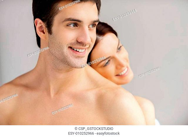 So good to be together. Cheerful young loving couple standing back to back and smiling