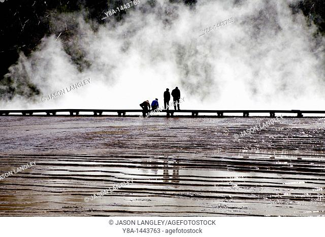 People standing against a steamy backdrop at Midway Geyser Basin, Yellowstone National Park, Wyoming, United States