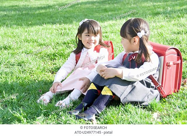 Girls Sitting on Grass and Talking