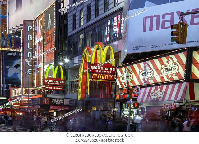 Bright neon signage flashes over crowds and taxi traffic zooming past Times Square the venue of the city's famous New. Mac Mc donald's Times Square New York...