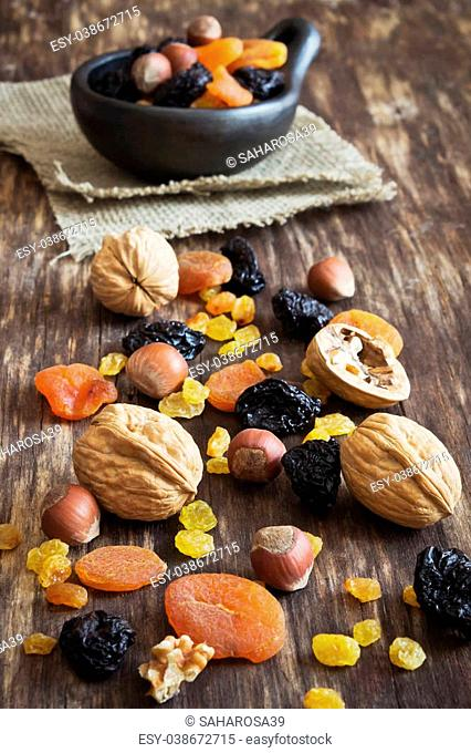 various dried fruits and nuts on an old wooden background. judaic holiday tu bishvat. health and diet food. selective focus