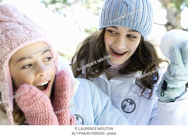 Two teenage girls smiling, one holding up snowball, both dressed in winter clothing