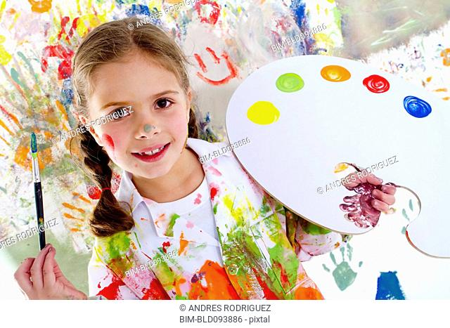 Hispanic girl covered in paint holding paintbrush
