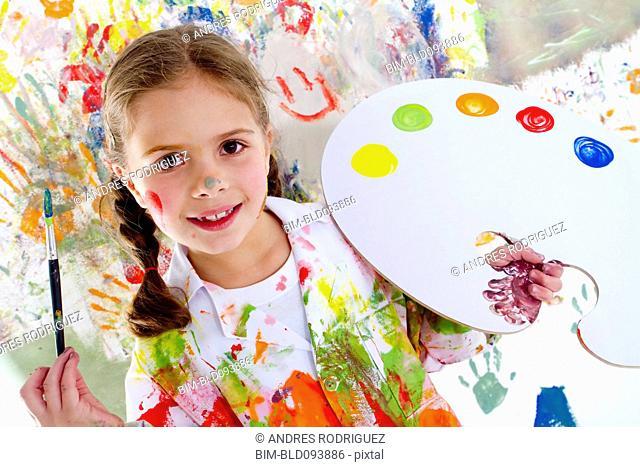 Hispanic girl covered in paint holding paintbrush